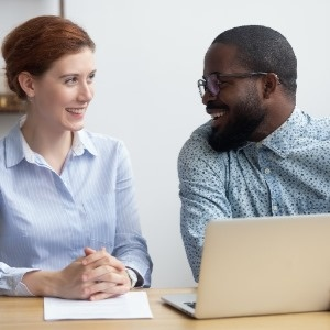 meeting between smiling female and smiling male coworkers working on laptop